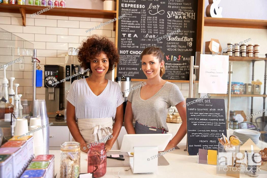 Stock Photo: Two women ready to serve behind the counter at a coffee shop.