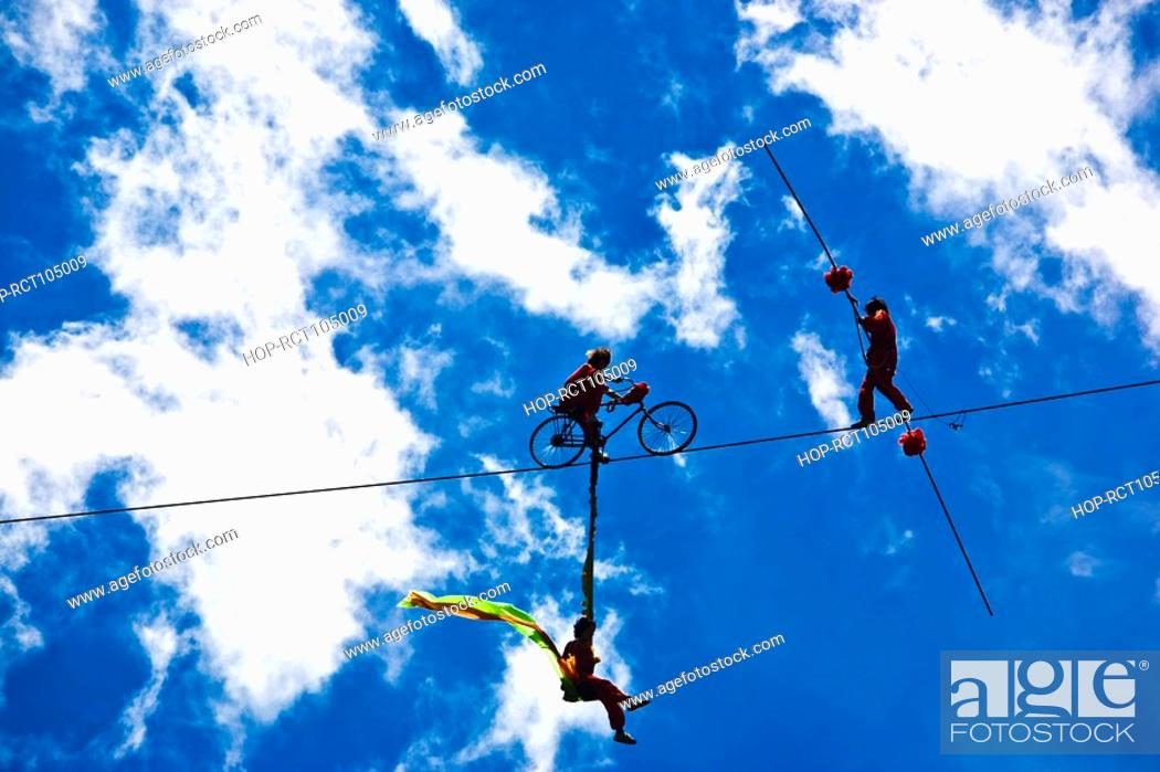 Stock Photo: Three performers performing stunt on a rope, Emerald Valley, Huangshan, Anhui Province, China.