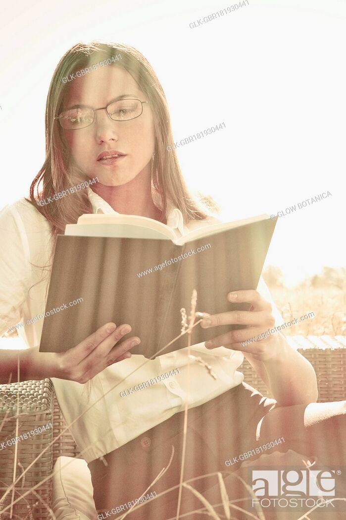 Stock Photo: Businesswoman reading a book on a sofa.