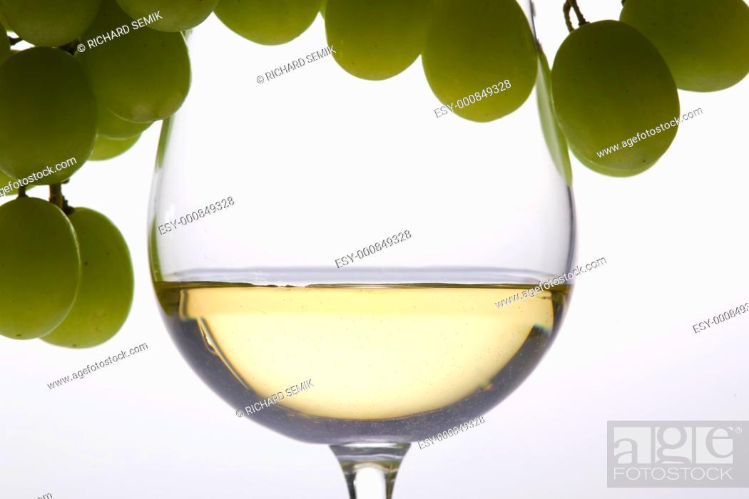 Stock Photo: wineglass with white wine and grape.