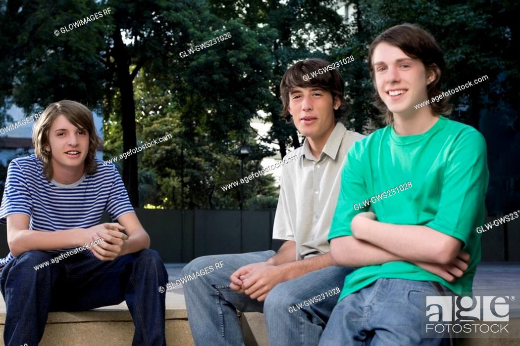 Stock Photo: Portrait of two teenage boys sitting with a young man and smiling.