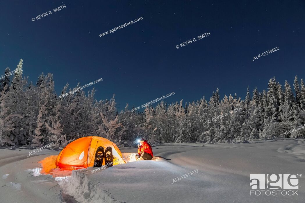 Imagen: Man with headlamp sits by a lit tent near an evergreen and snow covered forest, Gakona, Southcentral Alaska, Winter.