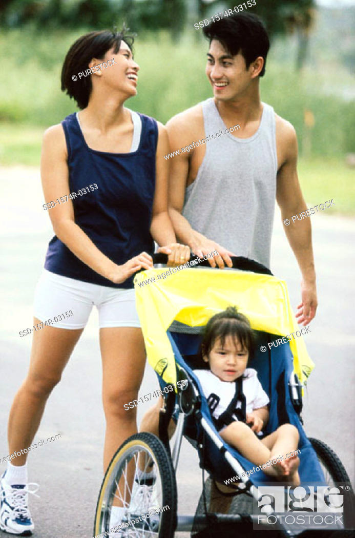 Stock Photo: Parents walking with their baby girl in a stroller.