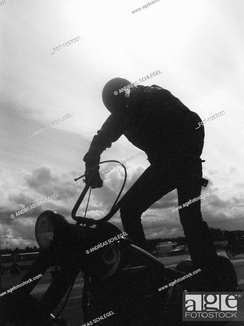 Stock Photo: A man standing on a motorcycle.