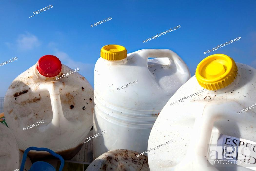 Stock Photo: oil bottles for recycling into a container of blue sky in recycling plant,botellas de aceite para reciclar dentro de un contenedor sobre cielo azul en planta de.