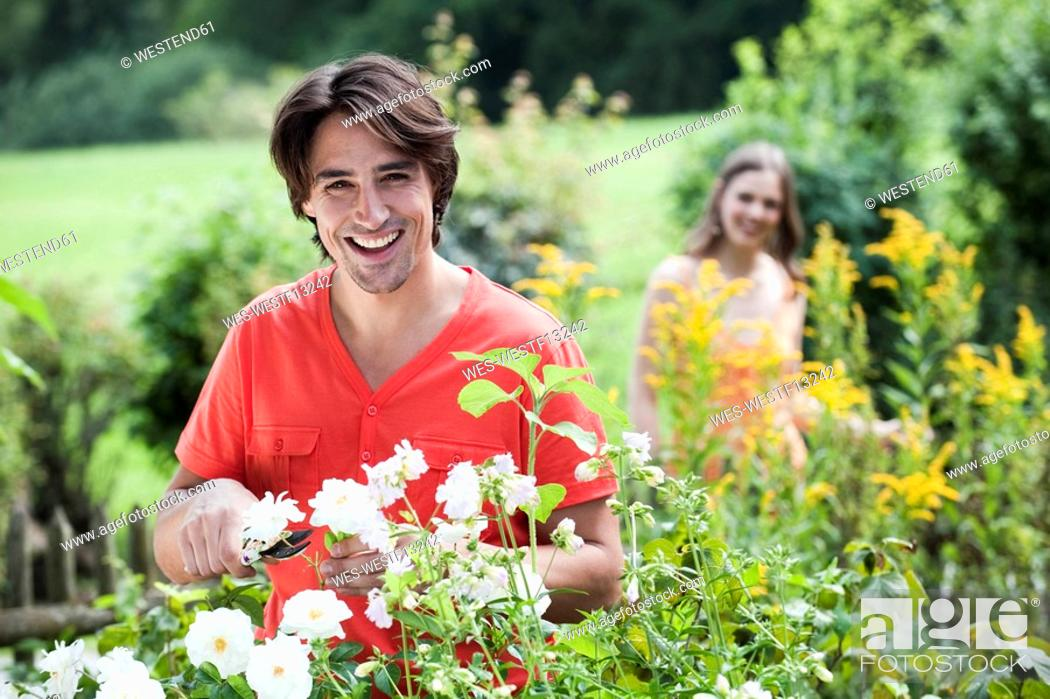 Stock Photo: Germany, Bavaria, Man pruning flowers, woman in background, smiling, portrait.