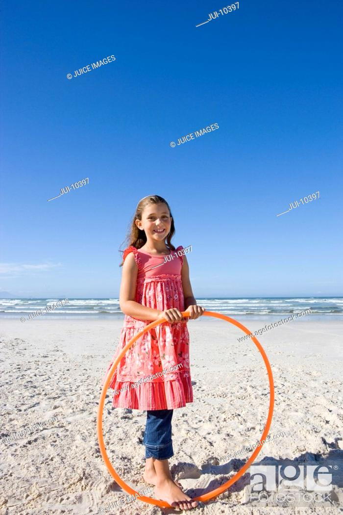 Stock Photo: Girl 5-7 with plastic hoop on beach, smiling, portrait.