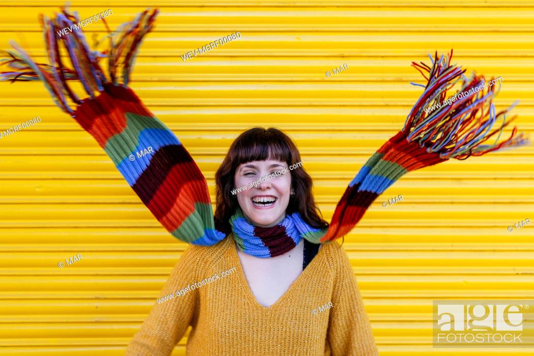 Stock Photo: Cheerful young woman with scarf around neck against yellow shutter.