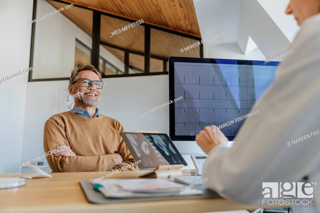 Stock Photo: Smiling patient talking with doctor while sitting at office.