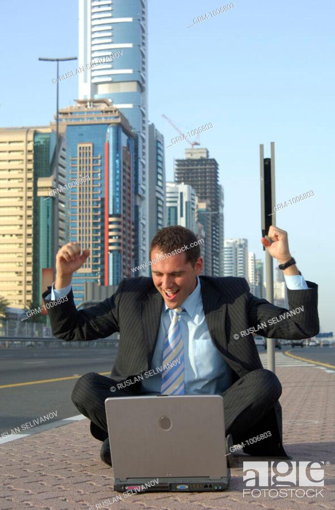 Stock Photo: Jubilating businessman with laptop on Shaikh Zayed Road in Dubai.