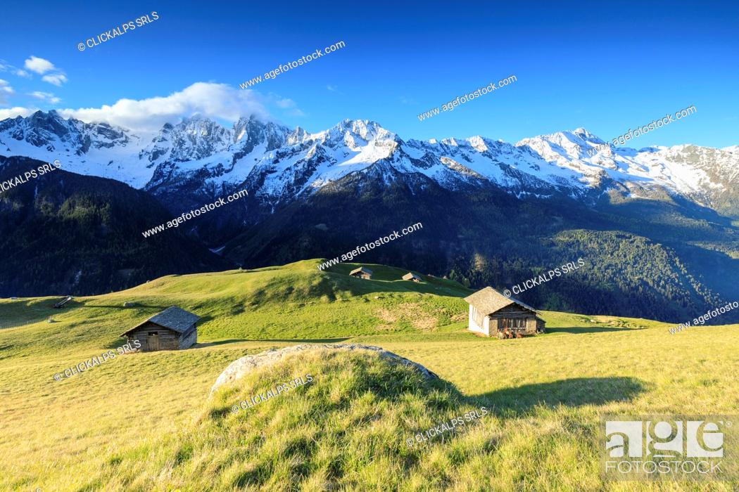 Stock Photo: Meadows and wooden huts framed by snowy peaks in spring Tombal Soglio Bregaglia Valley canton of Graubünden Switzerland Europe.