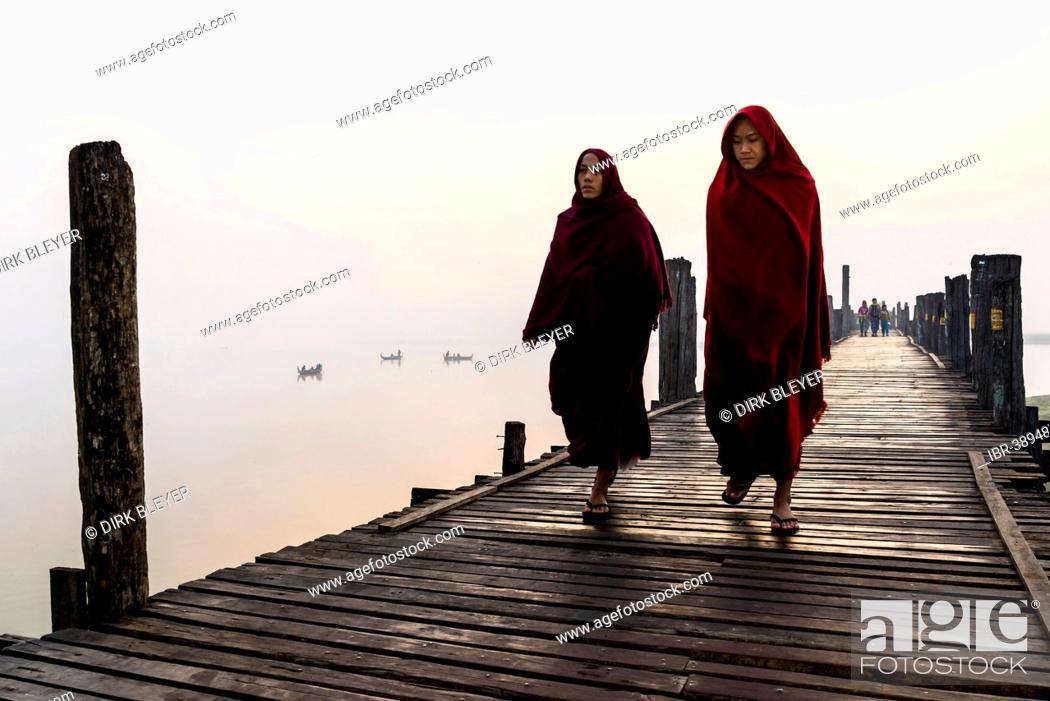 Stock Photo: Monks walking on a teak bridge, U Bein Bridge, across Thaungthaman lake, in the morning, Amarapura, Mandalay Division, Myanmar.