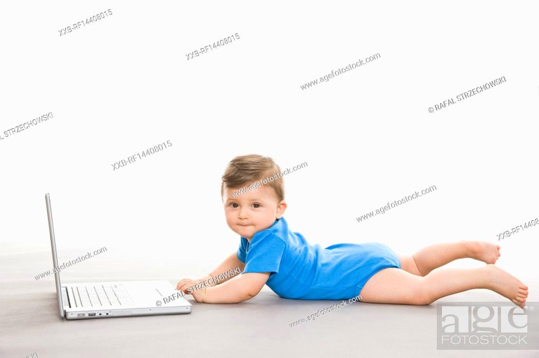 Stock Photo: Baby on floor with laptop.