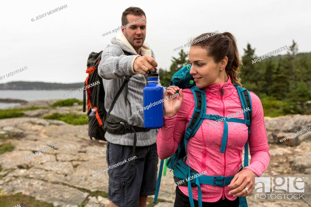 Stock Photo: Couple hiking on cloudy morning at Sand Beach in Acadia National Park, Maine, USA.