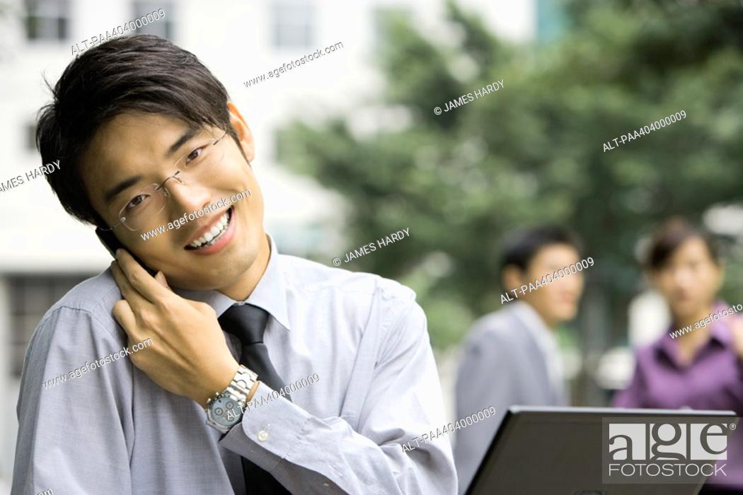 Stock Photo: Young businessman holding cell phone against shoulder, smiling at camera.