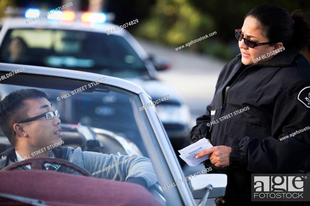 Stock Photo: Policewoman checking paperwork of man in convertible.