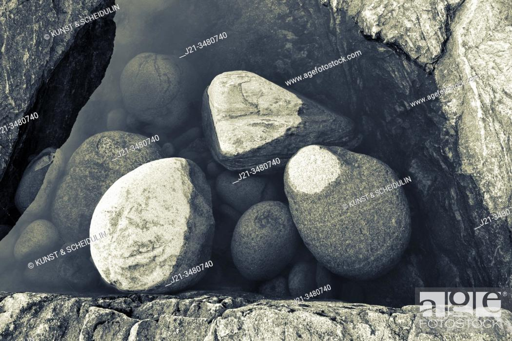 Stock Photo: Stones are lying in a puddle on a rocky beach - duotone blue and yellow. Västernorrland, Sweden, Europe.