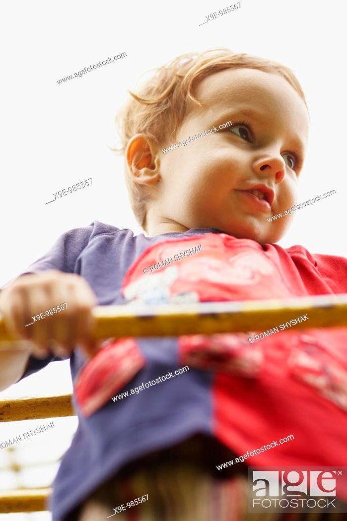 Stock Photo: A closeup portrait of a child on the ladder.