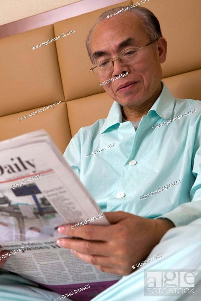 Imagen: Middle-aged man reading newspaper in bed.