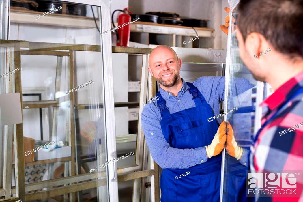 Stock Photo: Two workers inspecting windows at workshop.
