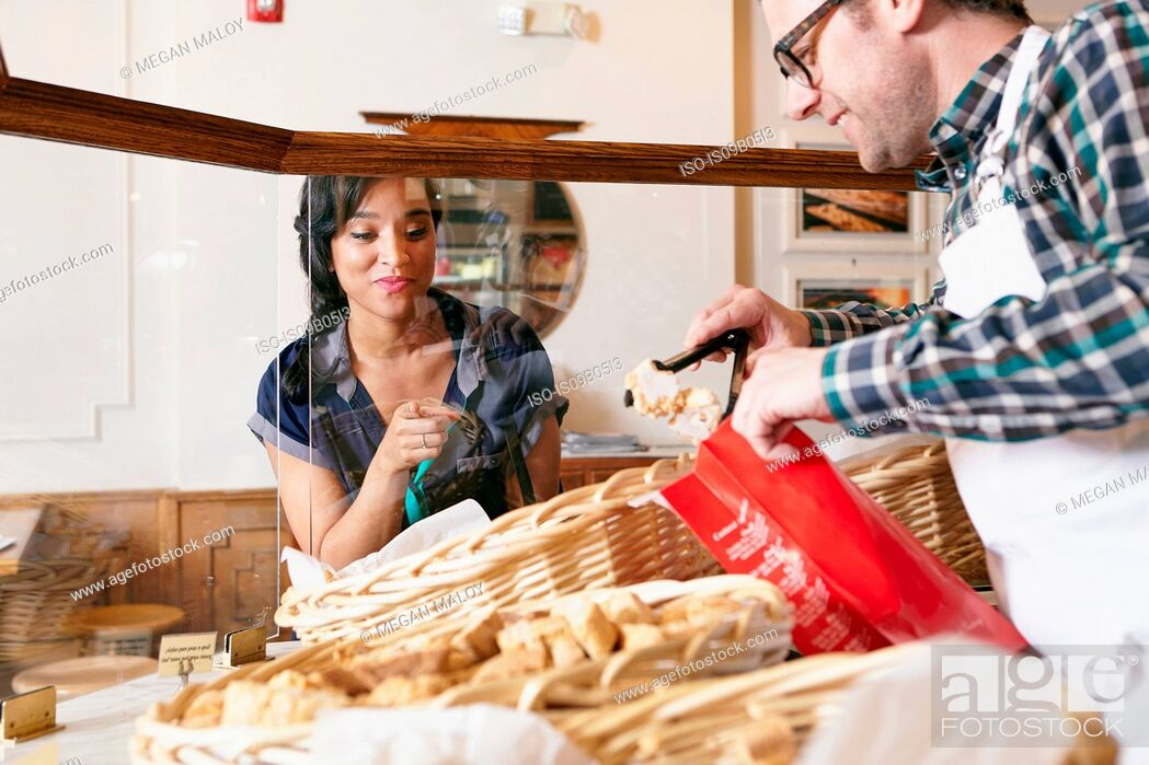 Stock Photo: Customer in bakery pointing to baked goods, worker placing goods in bag.