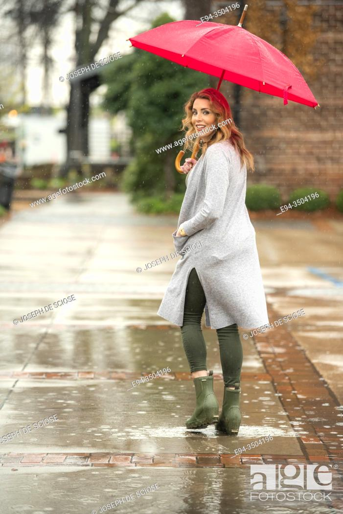 Photo de stock: A pretty 37 year old woman with an umbrella in the rain, looking over her shoulder at the camera.