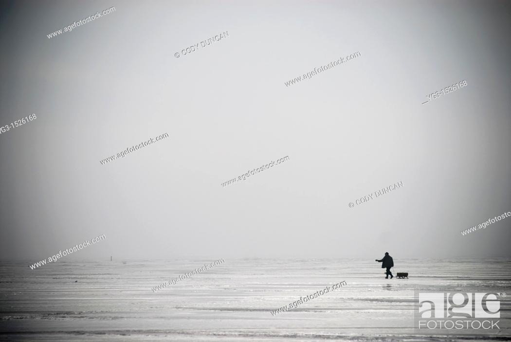 Stock Photo: Lone Ice fisherman walking across a frozen Curonian Lagoon, Lithuania.