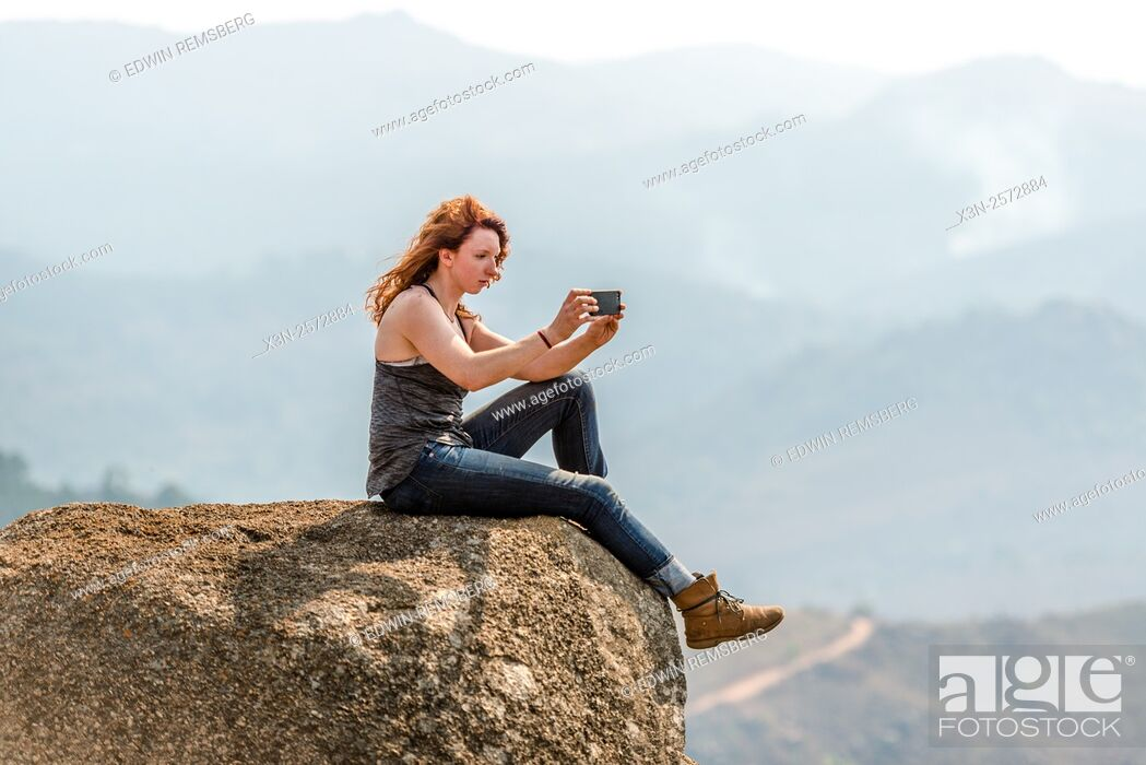 Stock Photo: Red-headed girl sitting on the edge of a boulder taking a photo of the landscape in the Mlilwane Wildlife Sanctuary in Swaziland, Africa.