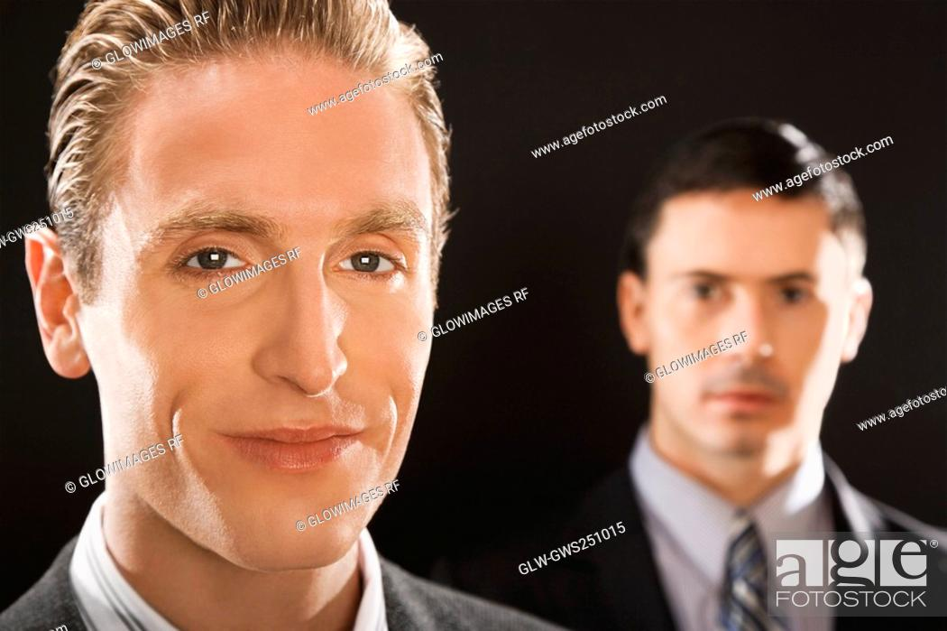 Stock Photo: Portrait of a businessman smiling with a businessman behind him.