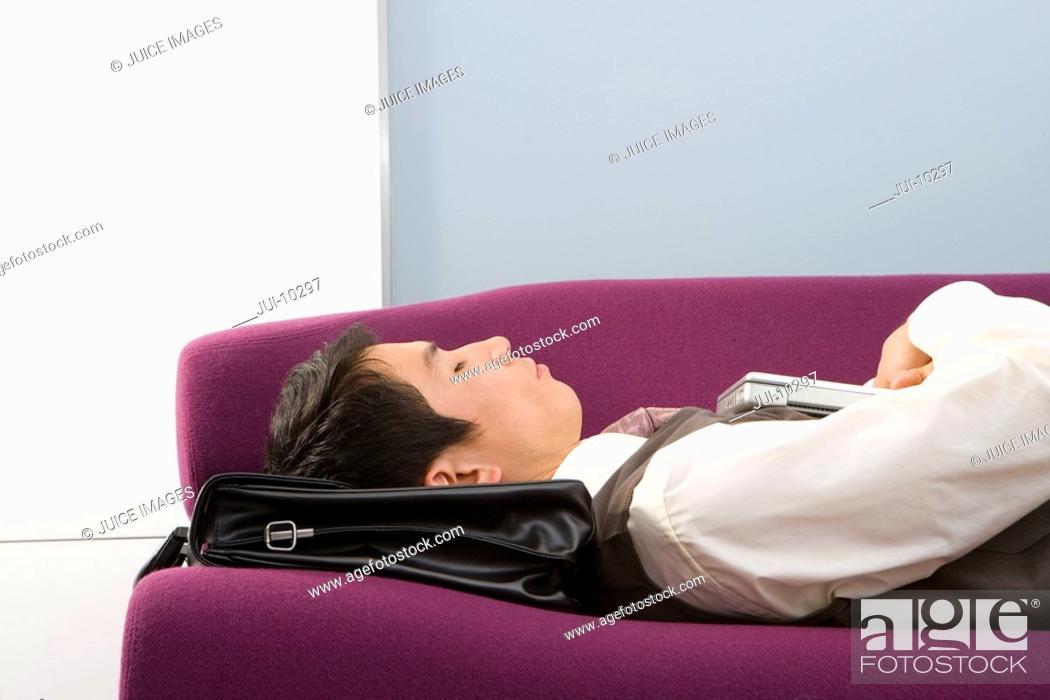Stock Photo: Businessman using briefcase as pillow, asleep on sofa, close-up.