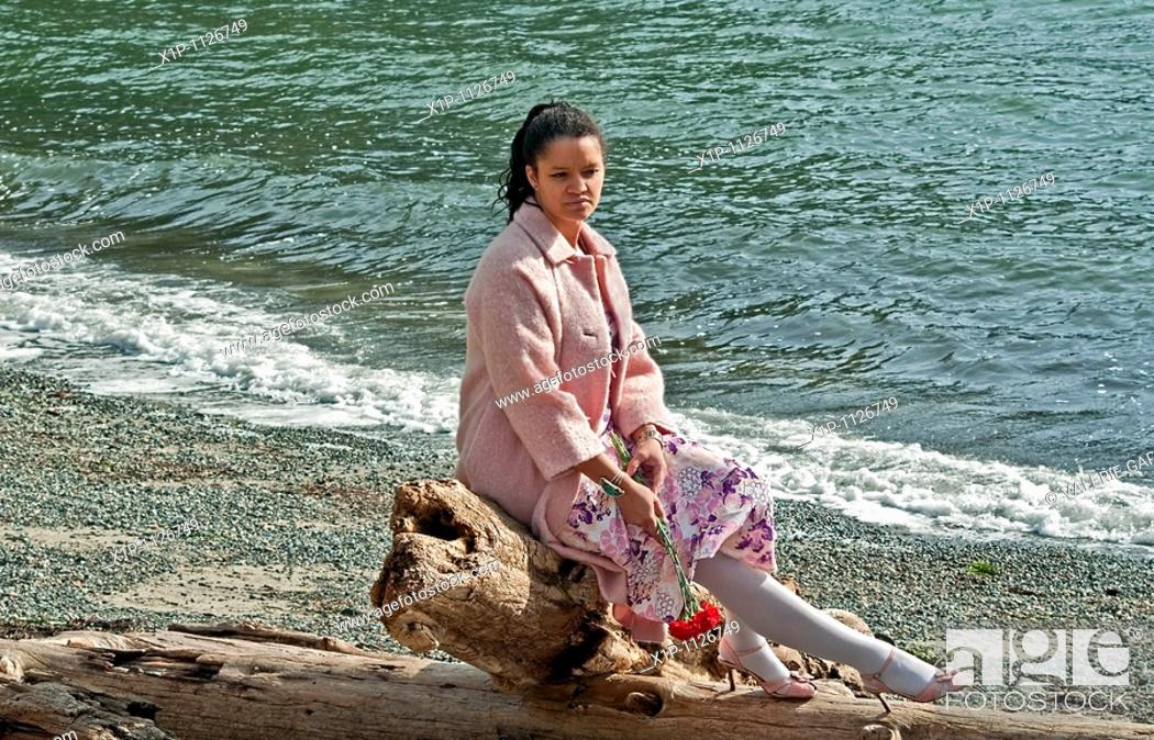Stock Photo: This pretty multi ethnic woman conveys many emotions, sadness, dejected, lonely as she's sitting on driftwood at a beach.