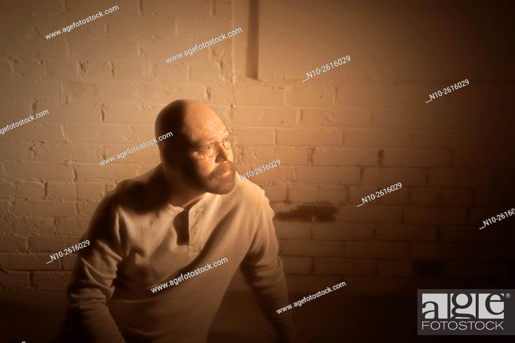 Stock Photo: Middle age bald man with a beard and glasses, sitting on the floor.
