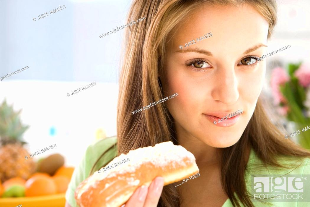 Stock Photo: Young woman with cream roll, portrait, close-up.