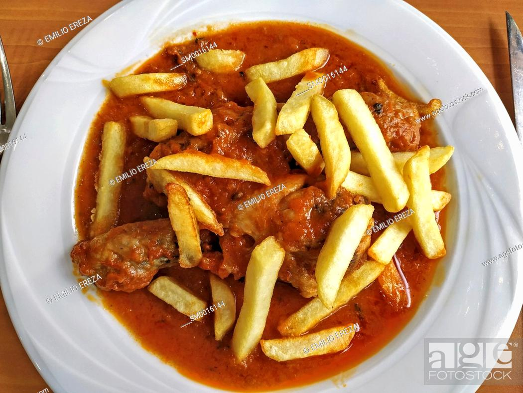 Stock Photo: Chicken legs with tomato sauce and potatoes.