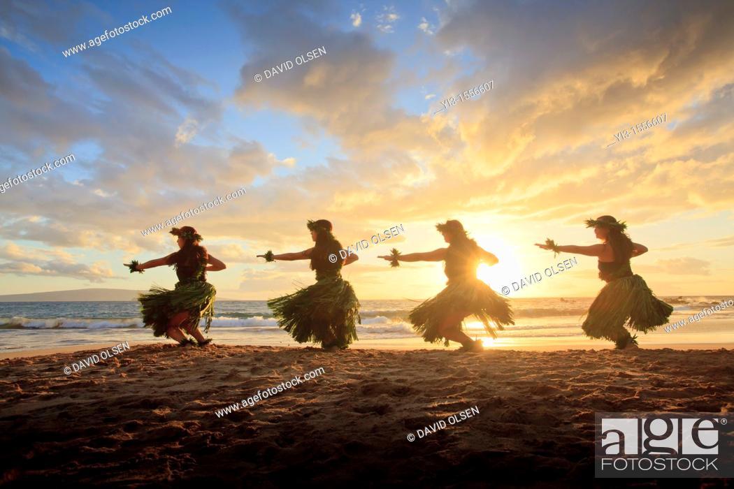 Stock Photo: Four hula dancers at sunset at Palauea, Maui, Hawaii, backlit by the sun.