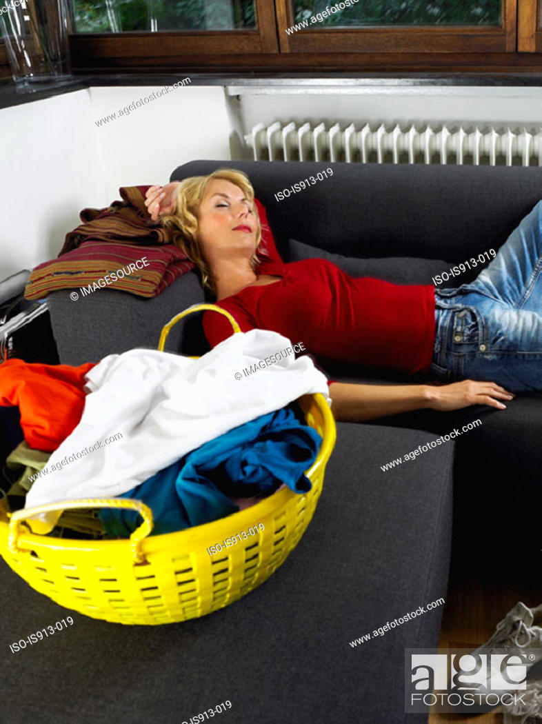 Stock Photo: Woman sleeping by laundry basket.