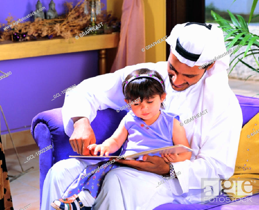Stock Photo: Father and daughter reading a book.