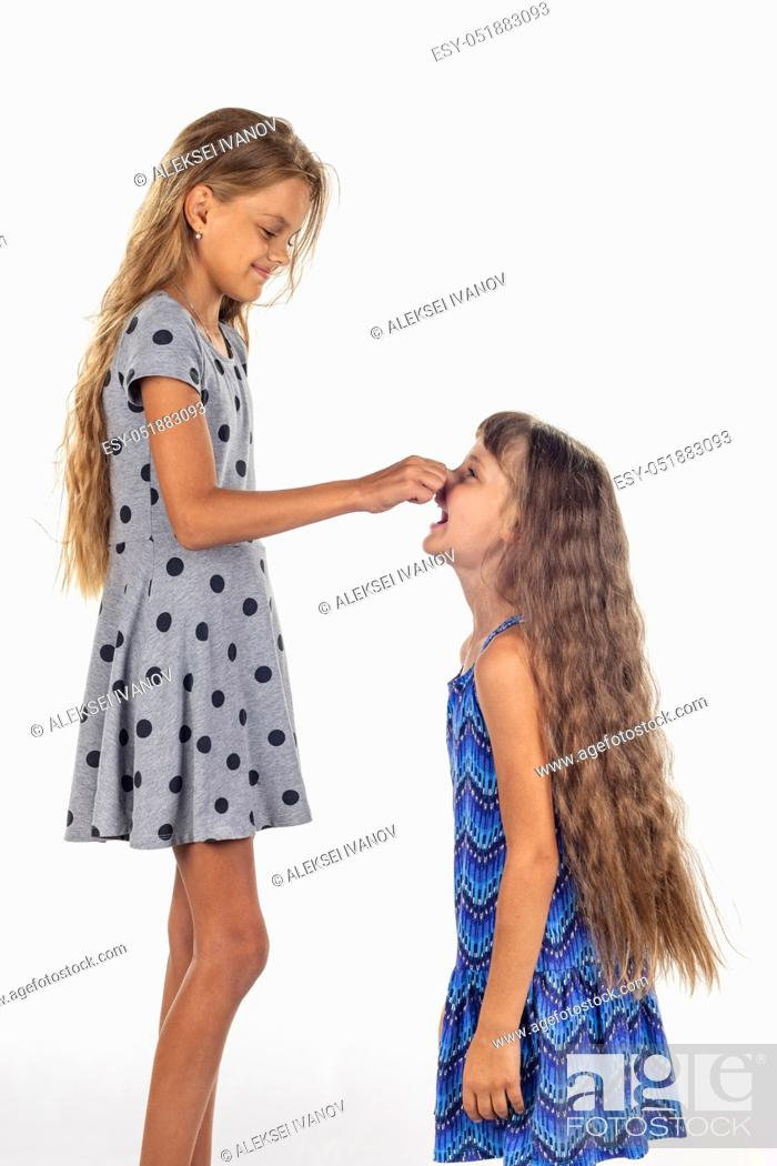 Stock Photo: Two girls of different stature, one stood on a chair and pulls the other girl by the nose.