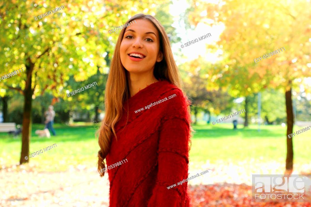 Stock Photo: Happy smiling girl wearing red poncho walking at park on Autumn season.