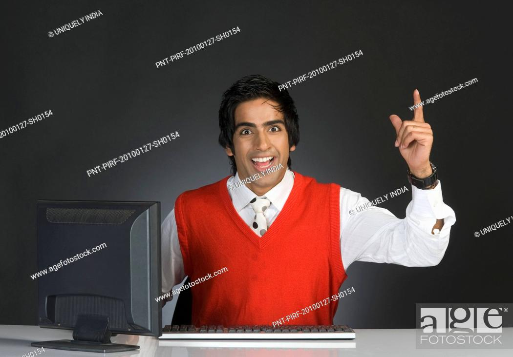 Photo de stock: Businessman pointing upward in front of a computer.
