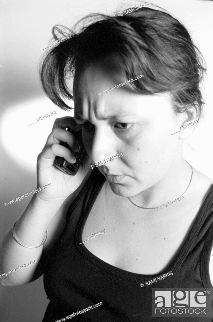 Stock Photo: Woman receiving bad news while talking on her mobile phone.