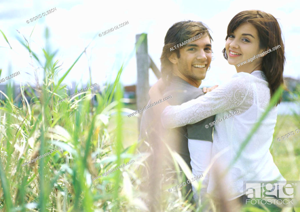 Stock Photo: Young couple outdoors, tall weeds in foreground.