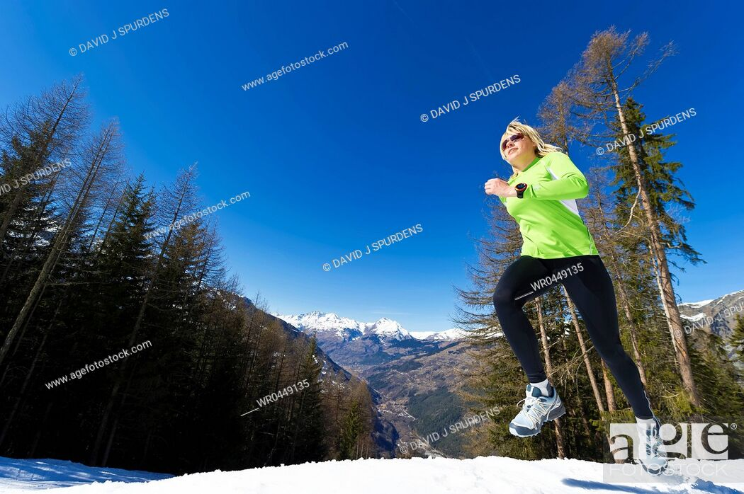 Stock Photo: A woman jogging in snowy mountains.