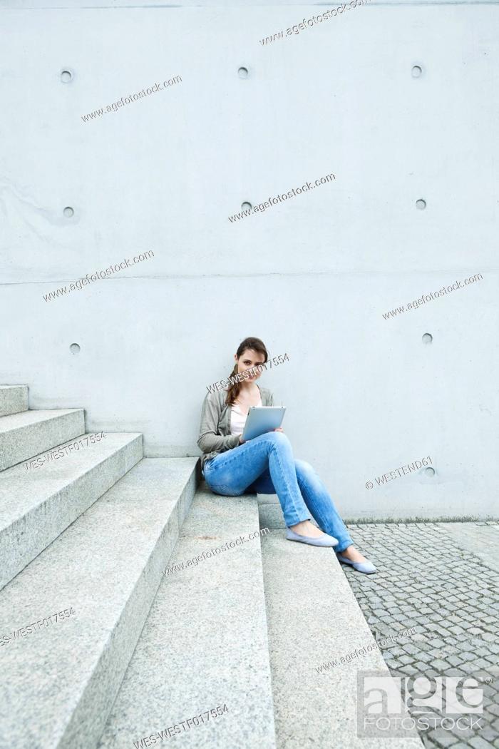 Stock Photo: Germany, Berlin, Woman using digital tablet on stairway.