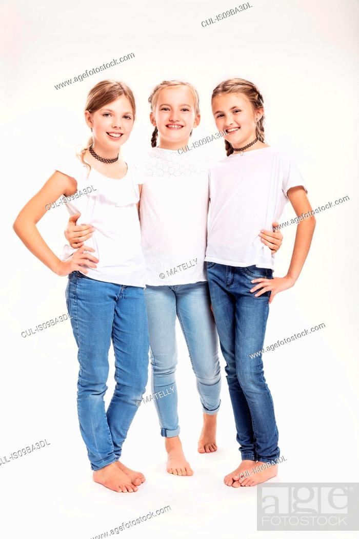 Stock Photo: Studio portrait of three girls posing with hands on hips.