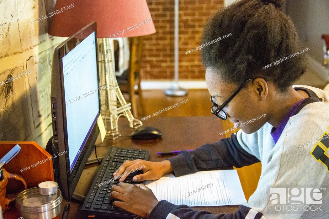 Stock Photo: African American teenager, with glasses, 15 years old, working on homework at her home in front of the desktop computer.