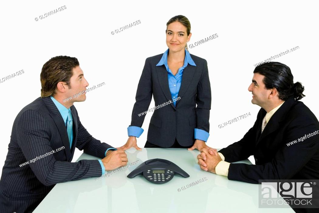 Stock Photo: Side profile of two businessmen and a businesswoman in a conference room.