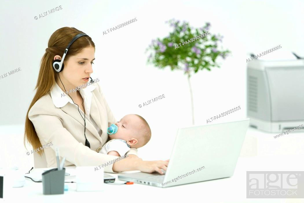 Stock Photo: Businesswoman in office, holding sleeping baby, using headset and laptop computer.