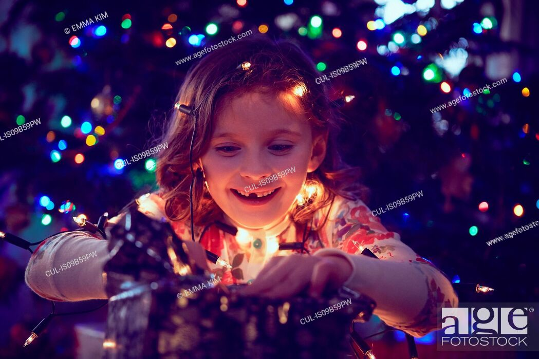 Stock Photo: Girl surrounded by lights wrapping christmas presents at christmas.