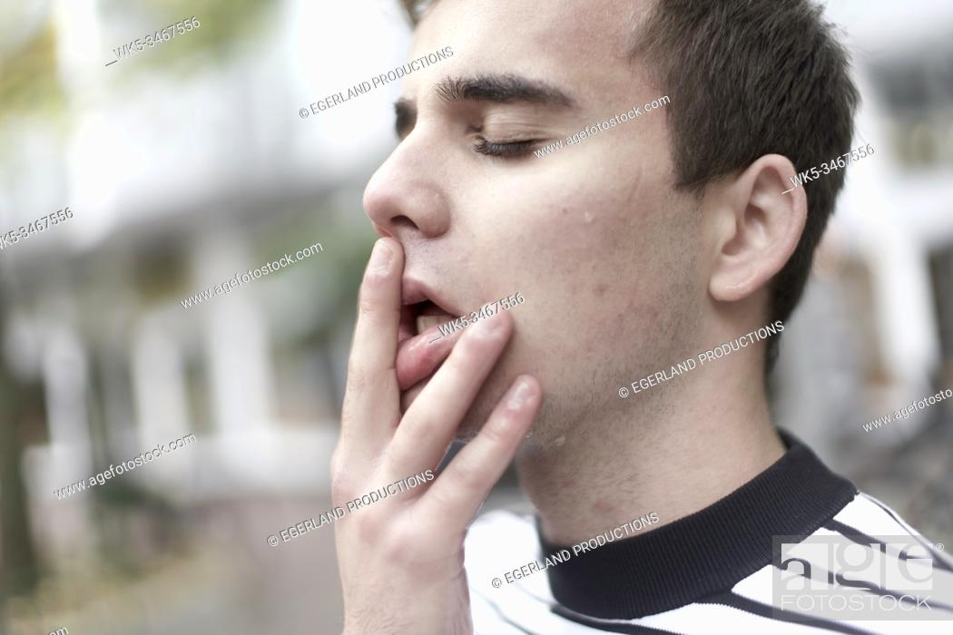 Stock Photo: Young man with hand on mouth. Munich, Germany.